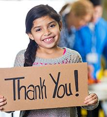 smiling girl holding homemade thank you Sign